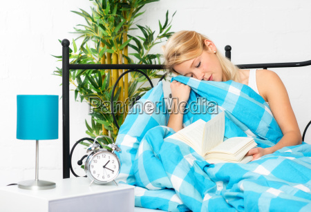 young woman reading to fall asleep