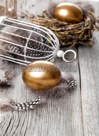 goldenes ei im nest auf hoelzernen