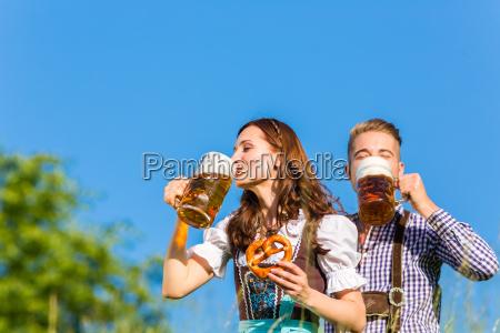 deutsches paar in tracht mit bier