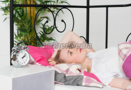 woman lying sleepless in bed thinking