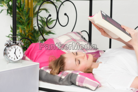 young woman reading before falling asleep