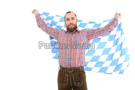 mann in tracht mit fahne