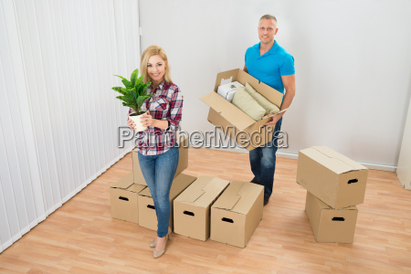 young couple moving boxes in new