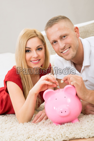 couple inserting coin in piggybank