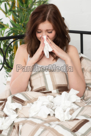 young woman with colds in bed