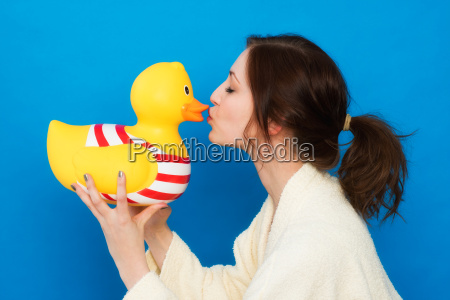 woman in bathrobe kisses a yellow