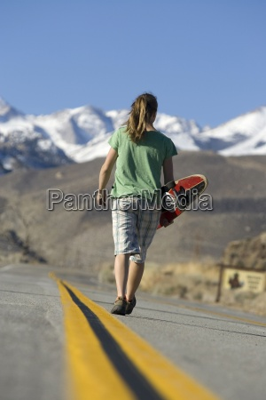 junge frau skateboarden in bishop kalifornien