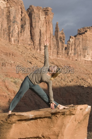 frau in yoga pose auf sandsteinfelsen