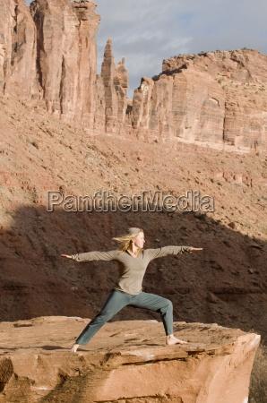 frau in der yogahaltung auf sandsteinfelsen