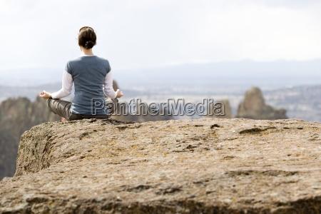 eine frau meditiert am rand einer