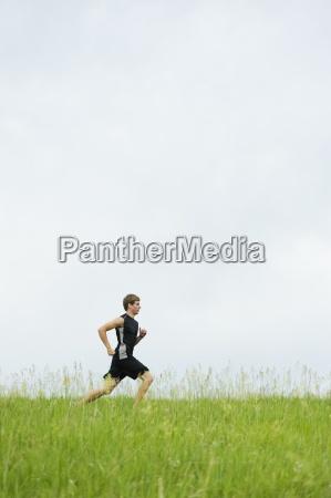 junger mann auf einem gras spur