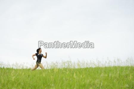 junge frau auf gras trail running