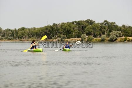 zwei maedchen in rettungswesten paddeln ihren
