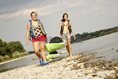 zwei maedchen in schwimmwesten laecheln als