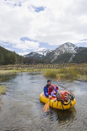ein junger mann paddelt mit seinem