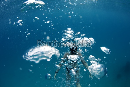 underwater view of a swimmer behind