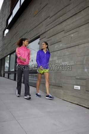 two girlfriends walking and talking in