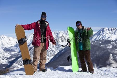 zwei aufgeregte junge erwachsene snowboarder in