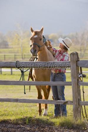 eine frau pflegt ihr pferd vor