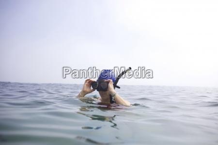 weiblicher schwimmer nimmt schnorchel weg nachdem