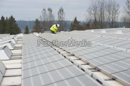 green energy technician adjusts photovoltaic panels