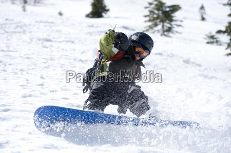 ein junge geniesst einen tag snowboarden
