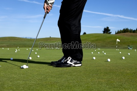 man lining up a putt while