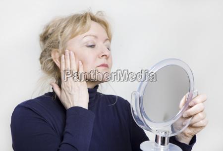 aeltere frau schaut in spiegel