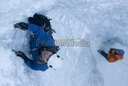 a professional female climber is belayed