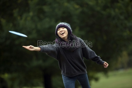 a young asian american woman throws