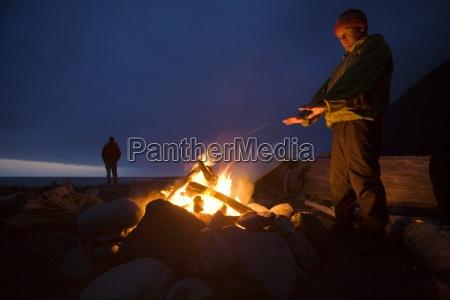 zwei maenner stehen um ein lagerfeuer