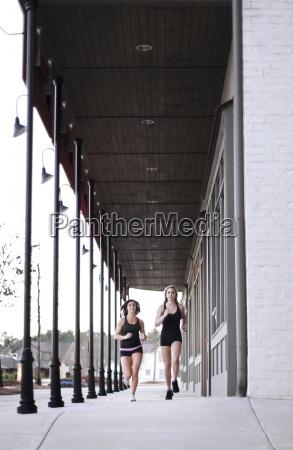 two women run on a sidewalk