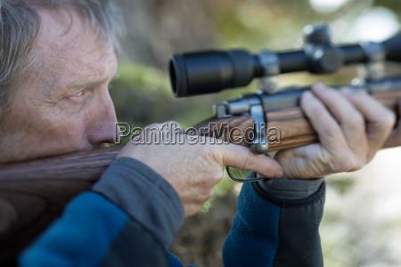 ein jaeger uebt mit einem gewehr