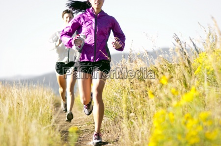 two young women trail running in