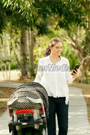 mutter mit baby im kinderwagen der