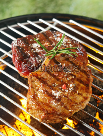 tender beef steaks grilling over the