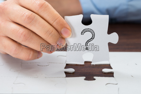 person hand holding puzzle with question