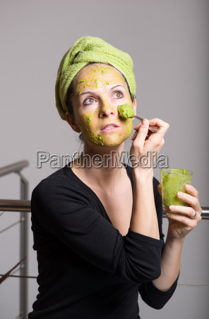 young woman with an avocado facial