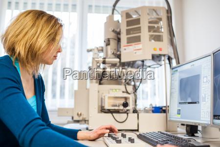 pretty female researcher using a microscope