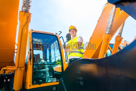 asian builder in excavator on construction