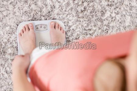 frau auf skala die gewichts verlust