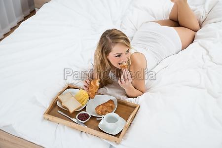 woman lying on bed having breakfast