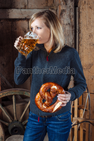 drinking beer and eating a pretzel