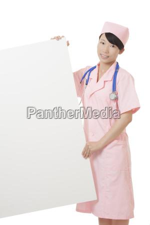 chinesische krankenschwester die ein weisses schild