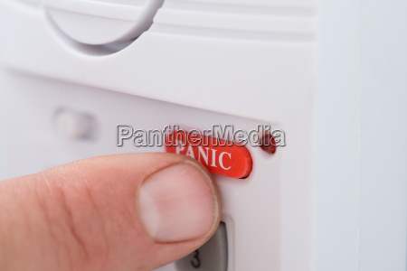 persons hand pressing panic button