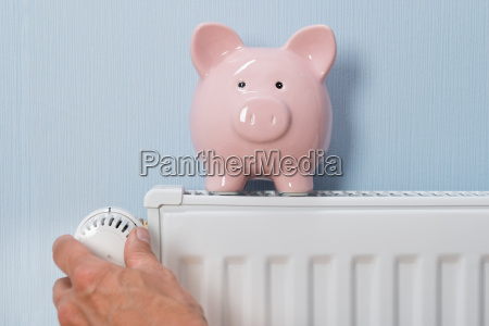 man holding thermostat with piggy bank