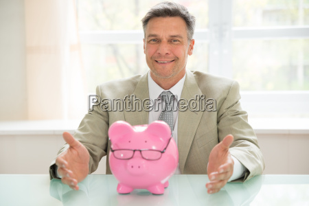happy businessman with piggybank on desk