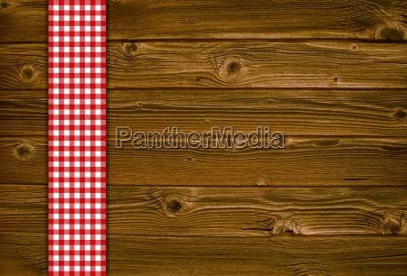 holzhintergrund mit rot weisser tischdecke