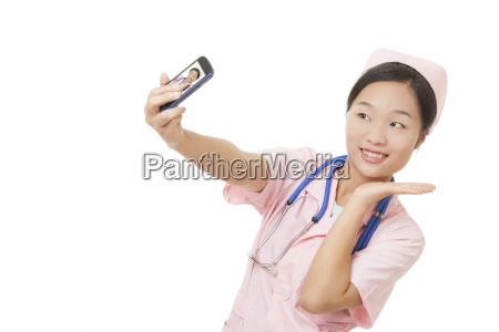 chinesische krankenschwester die eine zelle mit