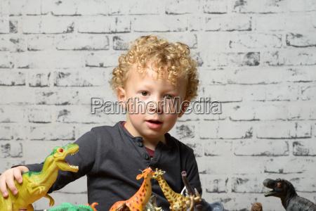 ein kleines kind spielt mit spielzeugtieren